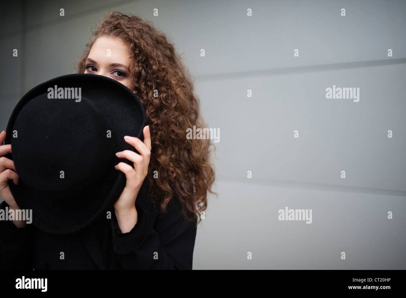 57ce9f90611 A young 20 year old slim attractive woman girl hiding her face behind a big  black hat UK