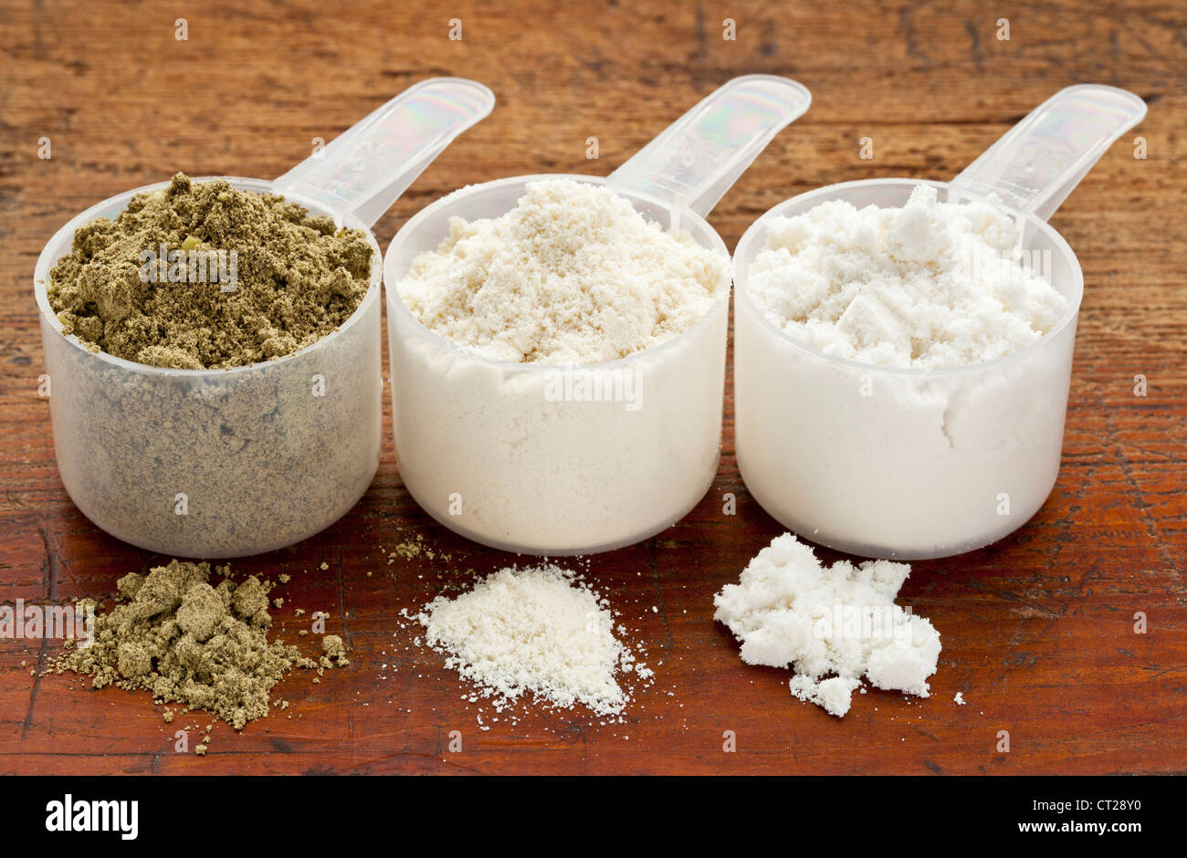 plastic measuring scoops of three protein powders (from left hemp seed, whey concentrate, whey isolate) on a grunge - Stock Image