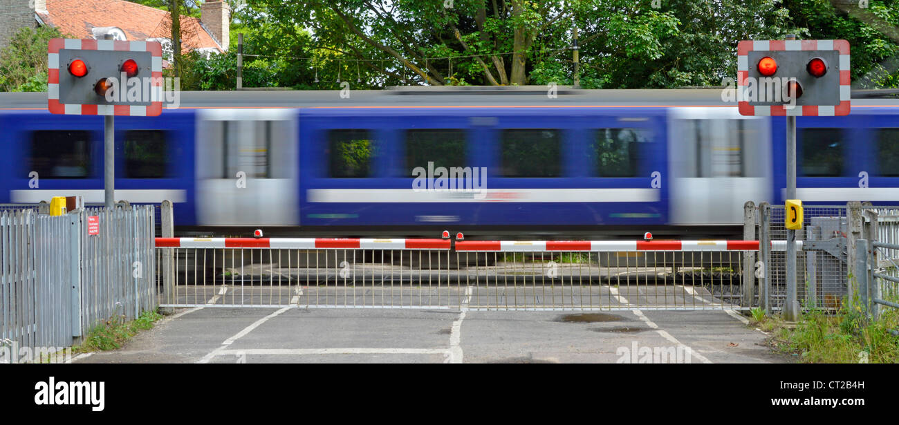 Railway tracks red flashing warning light sign level crossing barrier gates country road passenger train motion - Stock Image