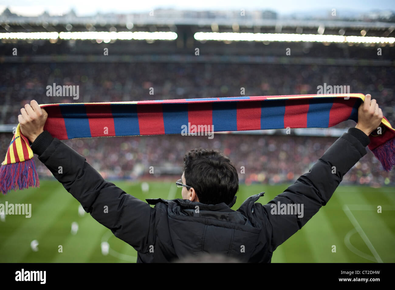 FC Barcelona fan holding a scarf with the colours of his team during a match in Camp Nou stadium - Stock Image