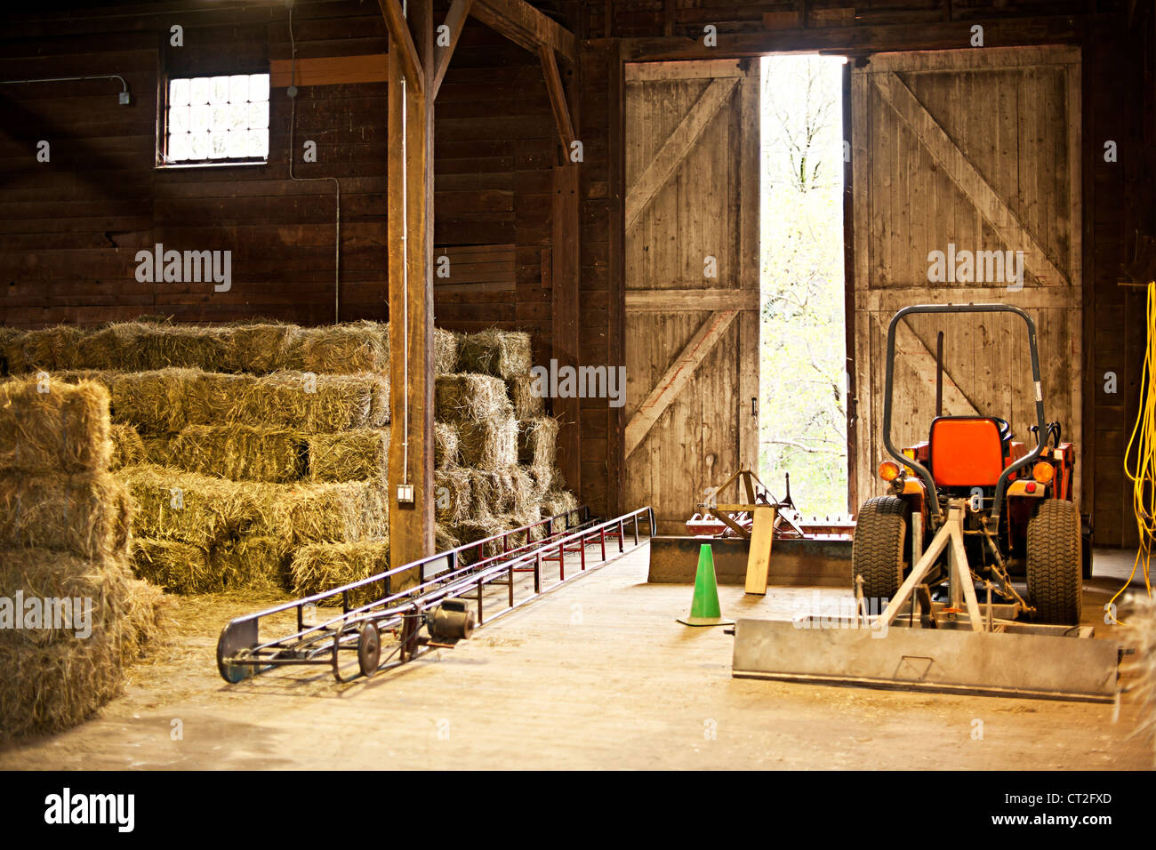 Interior of wooden barn with hay bales stacks and farm equipment - Stock Image