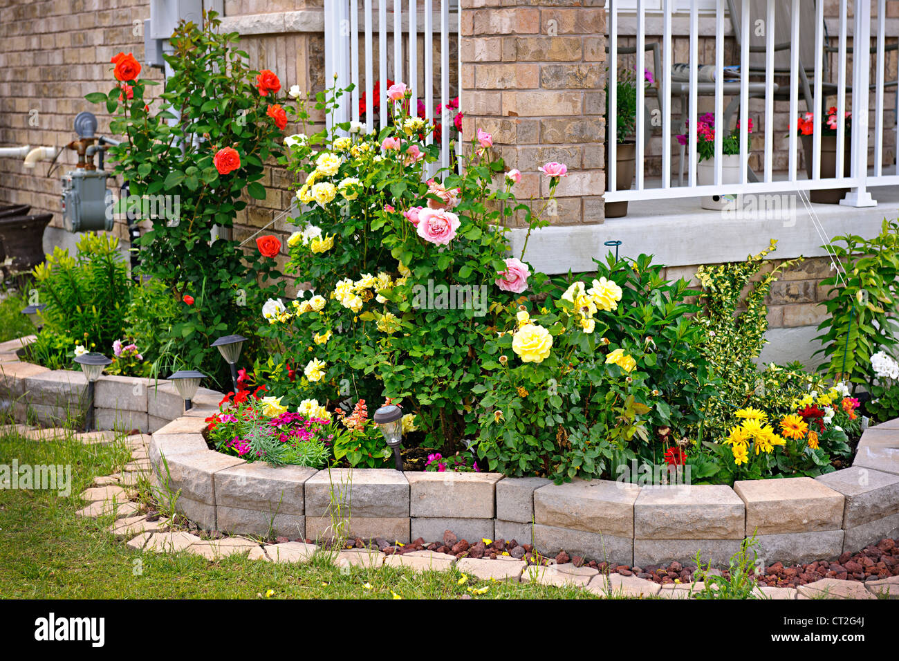 Natural stone landscaping in home rose garden - Stock Image