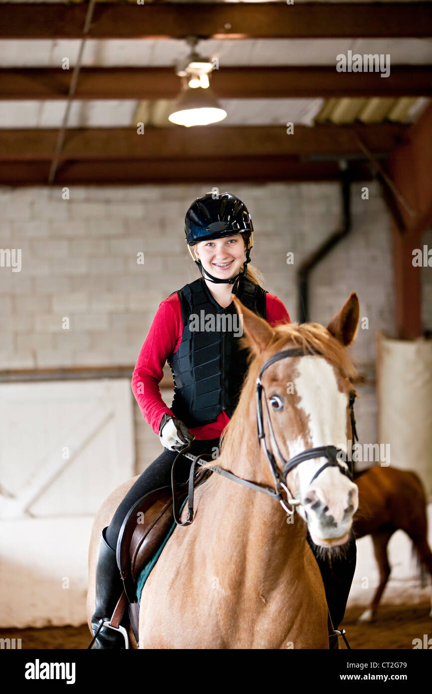Teenage girl on horseback wearing helmet and safety vest in indoor arena - Stock Image