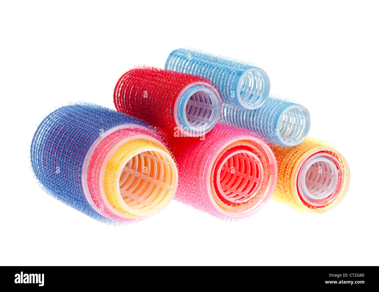 Colorful hair rollers stacked isolated on white background - Stock Image