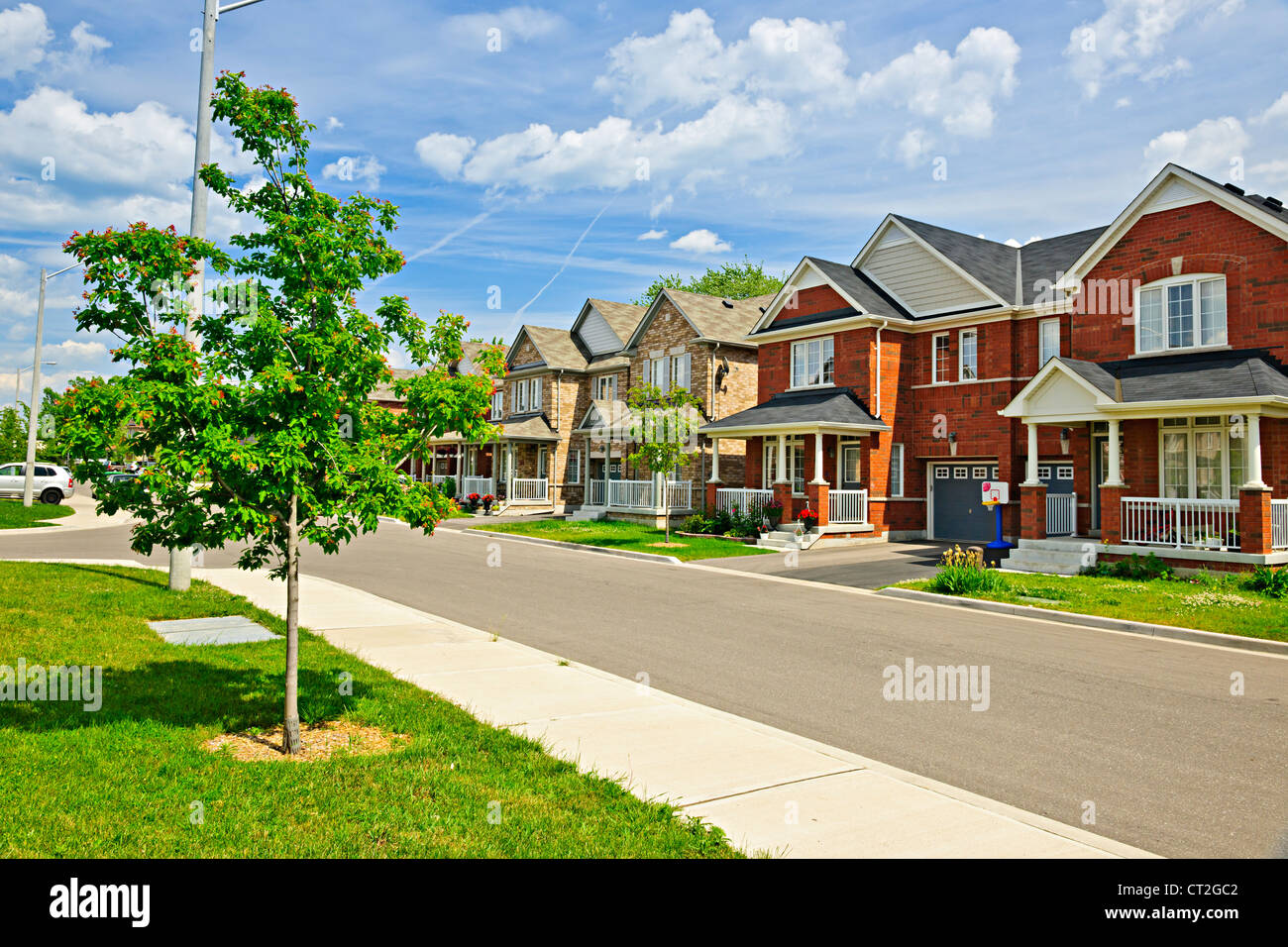 Suburban residential street with red brick houses - Stock Image