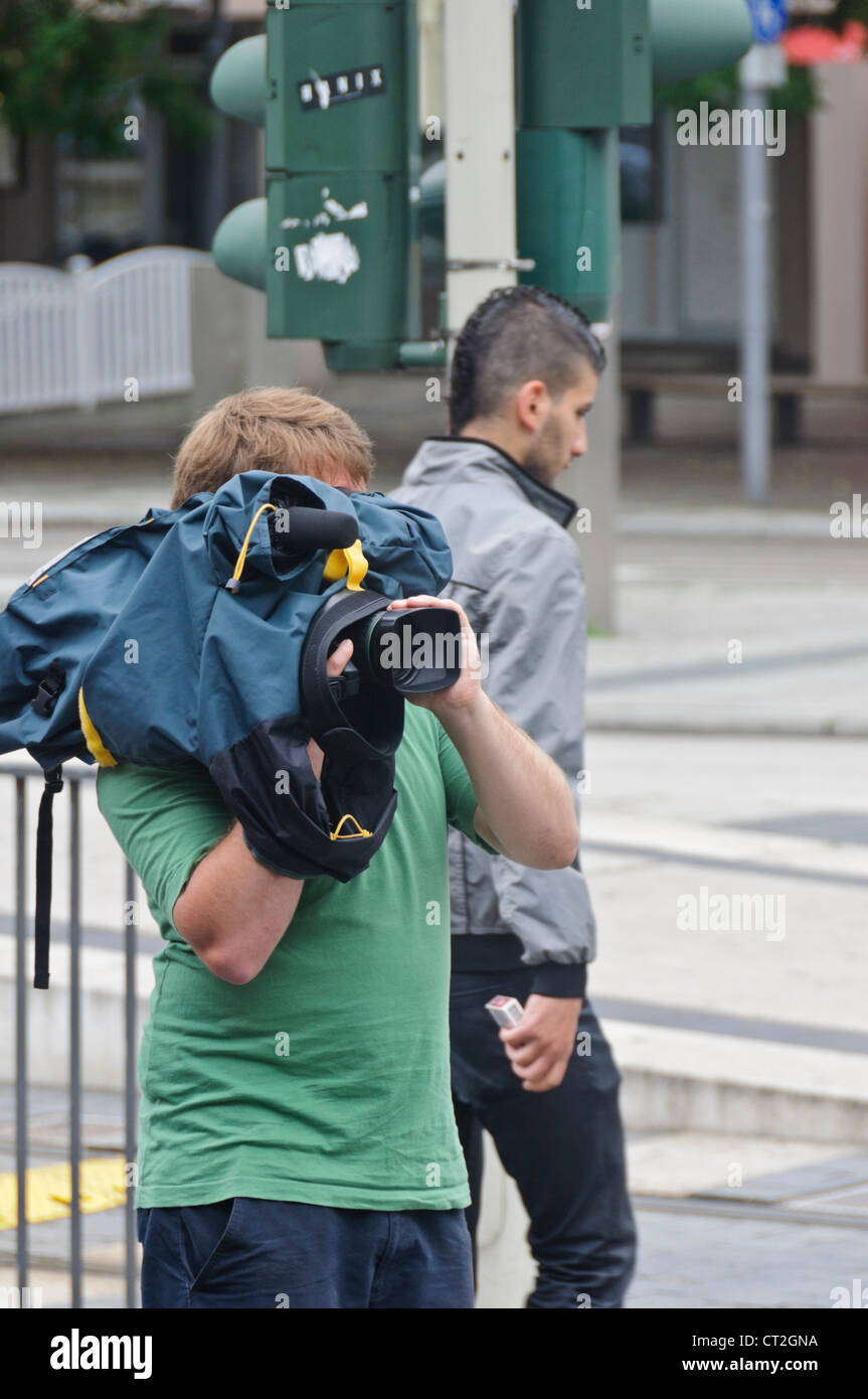 Young Cameraman with Digital TV Television Camera Rain Cover Protection - Heilbronn, Germany, Europe - Stock Image