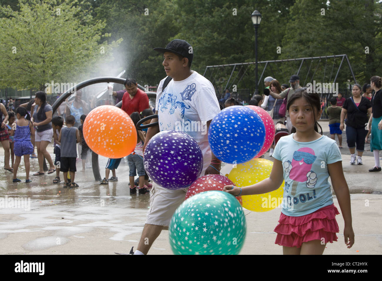 Children as well as adults cool off in the water area of a playground in Prospect Park, Brooklyn, NY on a hot summer - Stock Image
