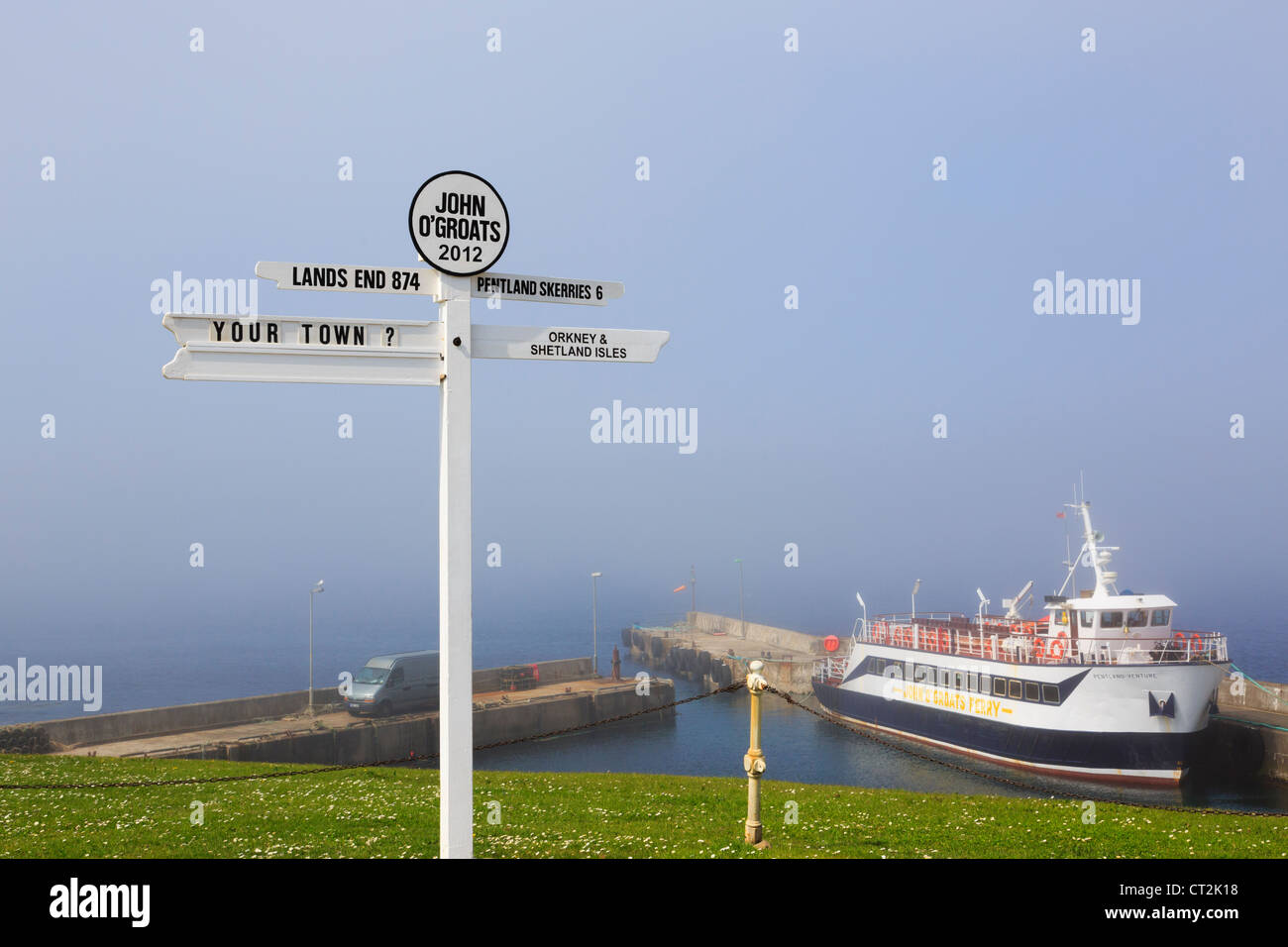 Scene with signpost and ferry boat with sea mist on the north eastern coast at John o' Groats Caithness Scotland - Stock Image