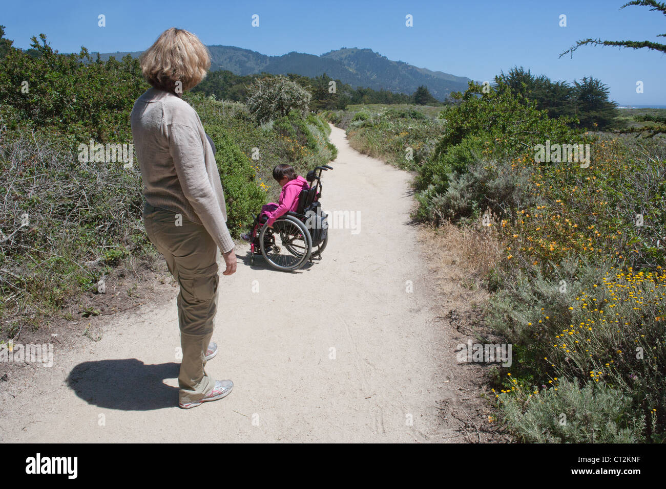 Mom watching her seven year old daughter with muscular dystrophy steer her wheelchair on dirt hiking trail. - Stock Image