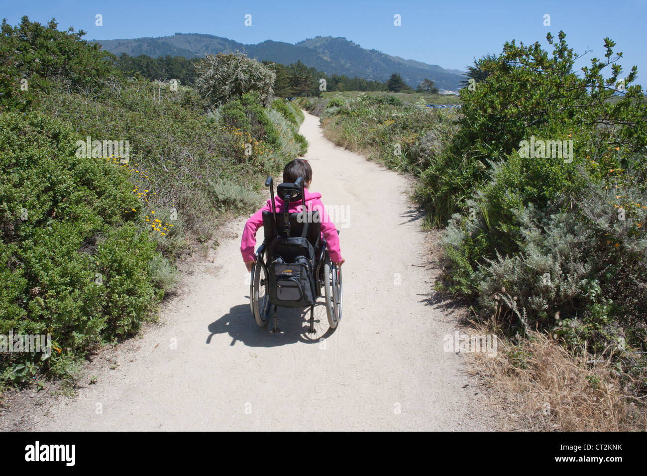 Seven year old girl with muscular dystrophy takes herself on a hiking path, Point Lobos, CA - Stock Image