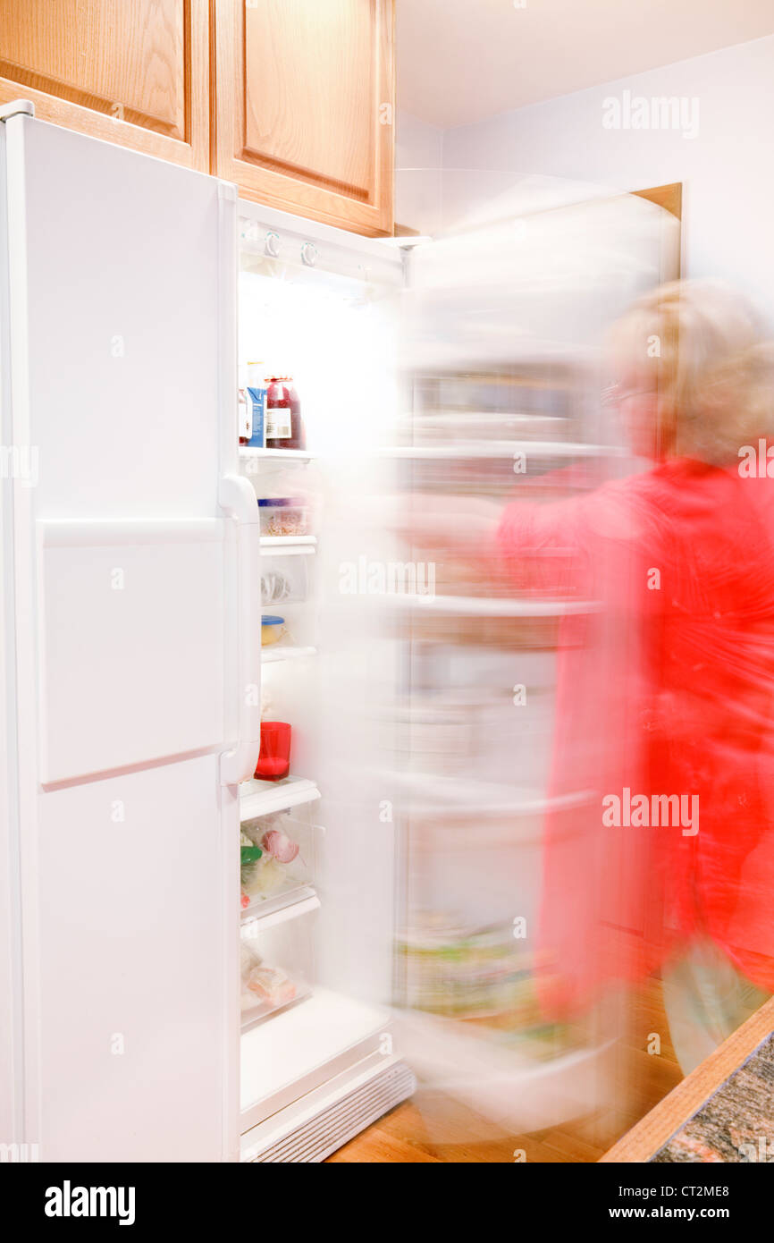Woman busily moving about - getting things out of the refrigerator - Stock Image