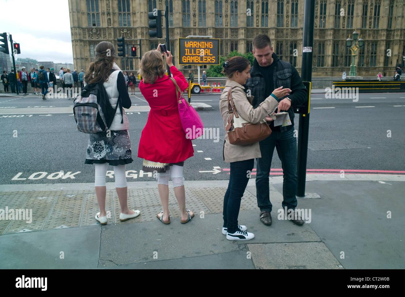 A group of tourists on Westminster Bridge London with an electronic sign opposite  warning Tourists about illegal - Stock Image