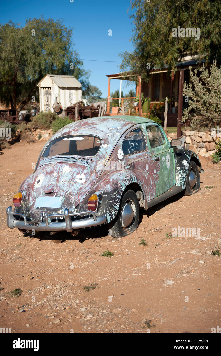 Colourful painted VW beetle car in front of a historic homestead of Silverton, Outback New South Wales, Australia - Stock Image
