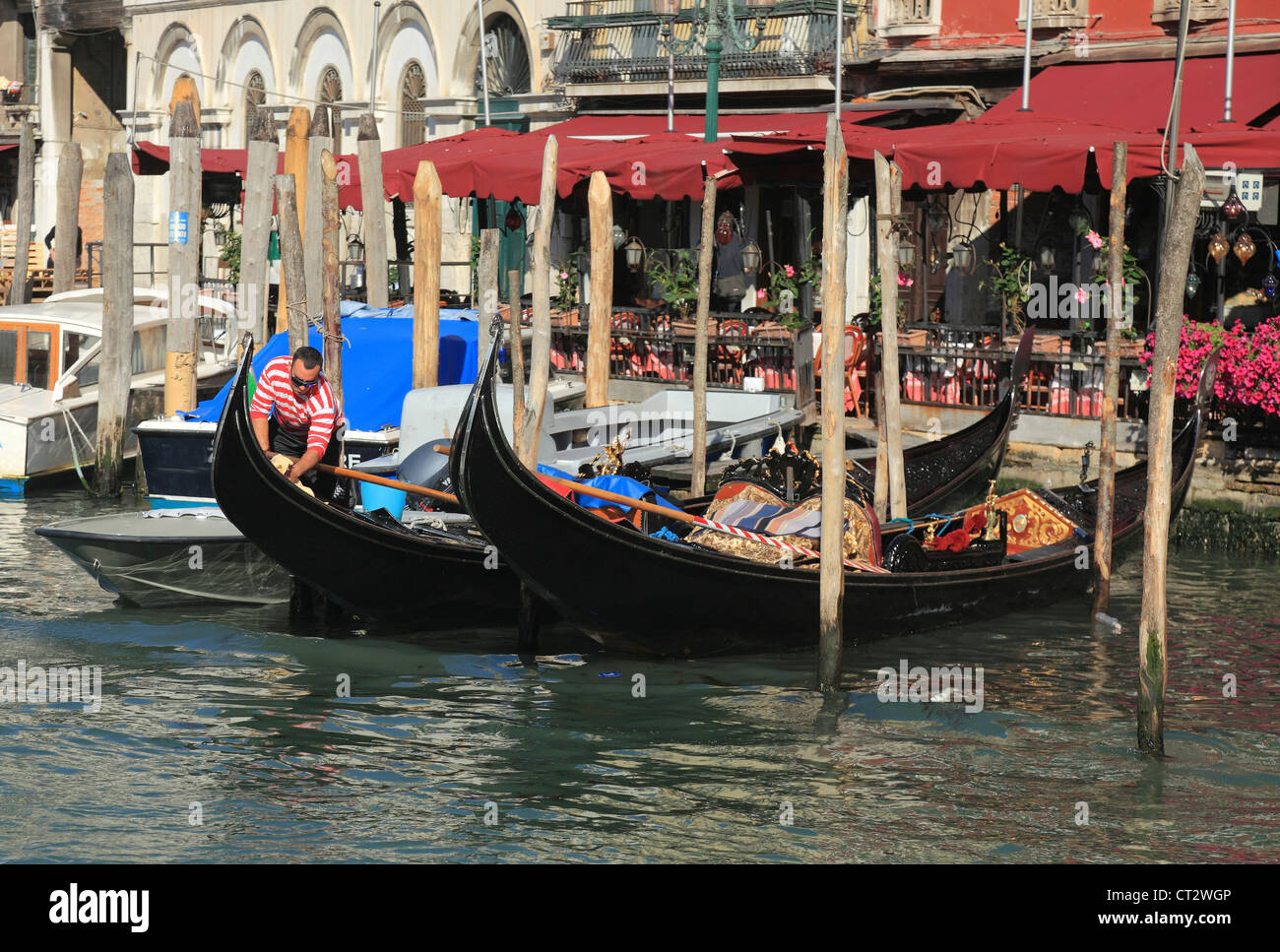 Gondolier preparing gondolas for trip on Grand Canal. - Stock Image