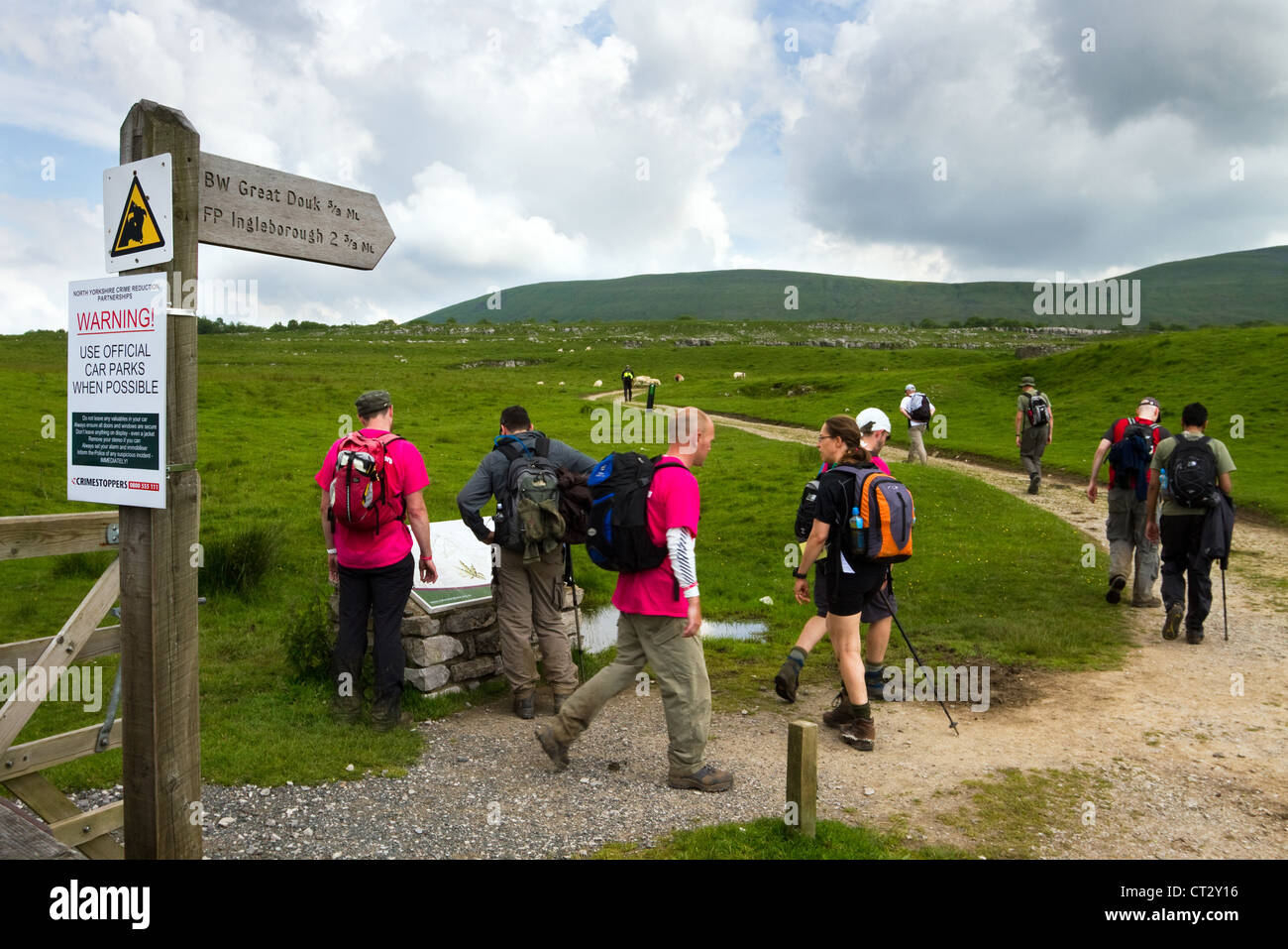 Hiking team, men & women ascending Great Douk and Ingleton_ Signposted route for group of walkers to ascend - Stock Image