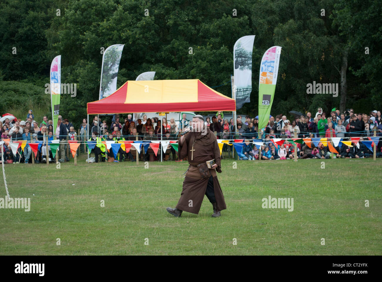 Man in medieval monk costume dressed as Friar Tuck at jousting tournament with crowd and pavilion background - Stock Image