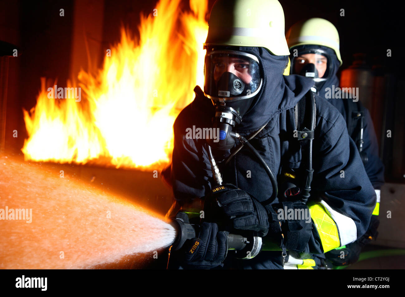 Fire service, fire men, fire fighting training at a fire training house. Firefighters with breathing apparatus. - Stock Image