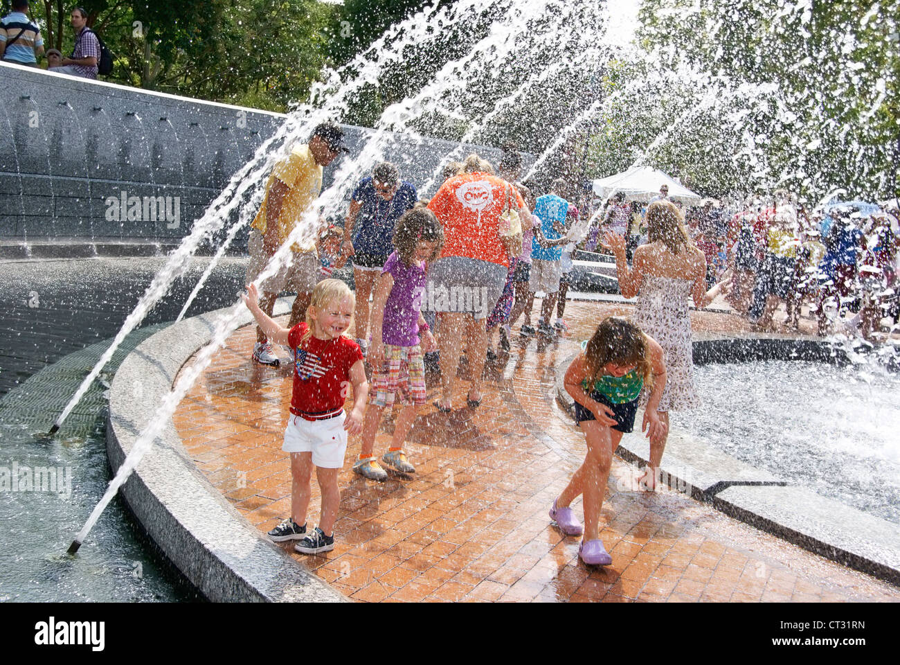 Children and adults finding relief in the Center City Park fountain, Greensboro NC, during hot weather 4th of July - Stock Image