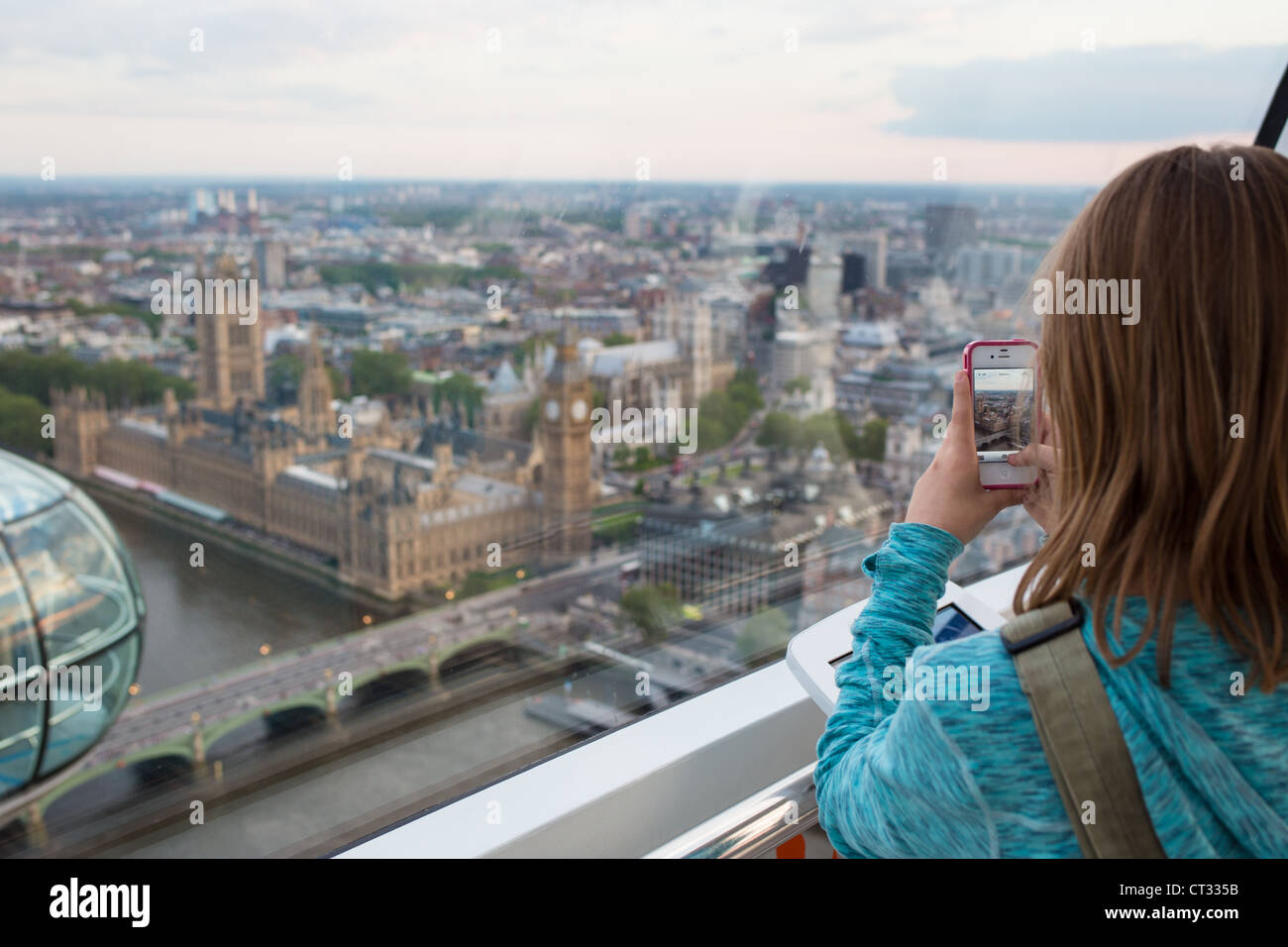 A young girl takes a photo from the London Eye - Stock Image