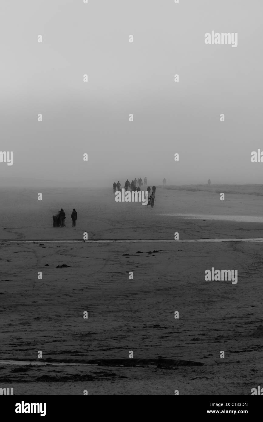 People on the beach in the mist - Stock Image