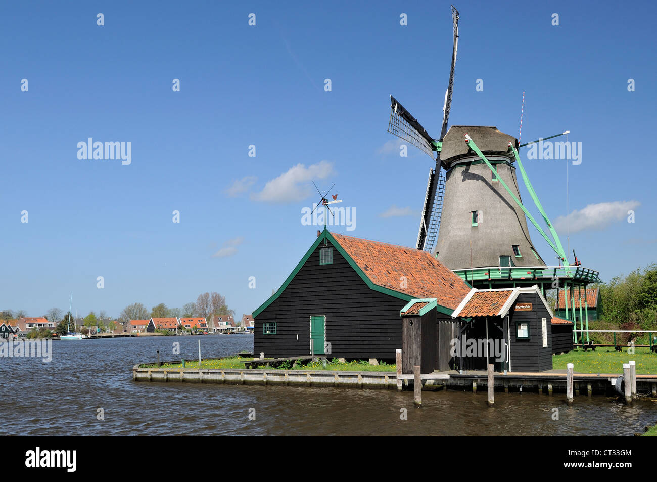 windmill on river, Zaanse Schans view of traditional windmill at touristic location, shot in bright spring light - Stock Image