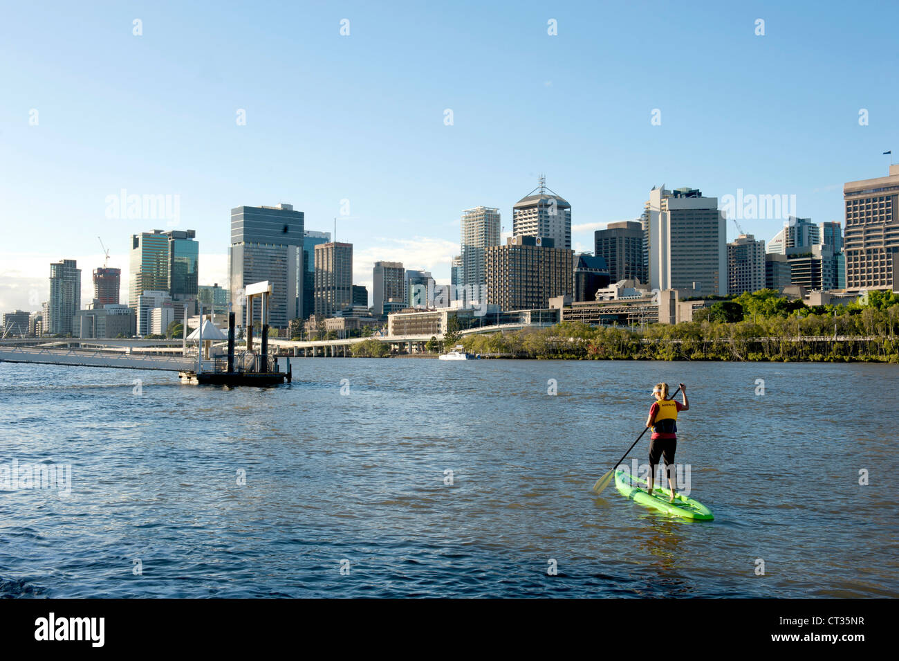 A woman doing stand-up paddling on Brisbane River with the CBD in view, Queensland, Australia - Stock Image