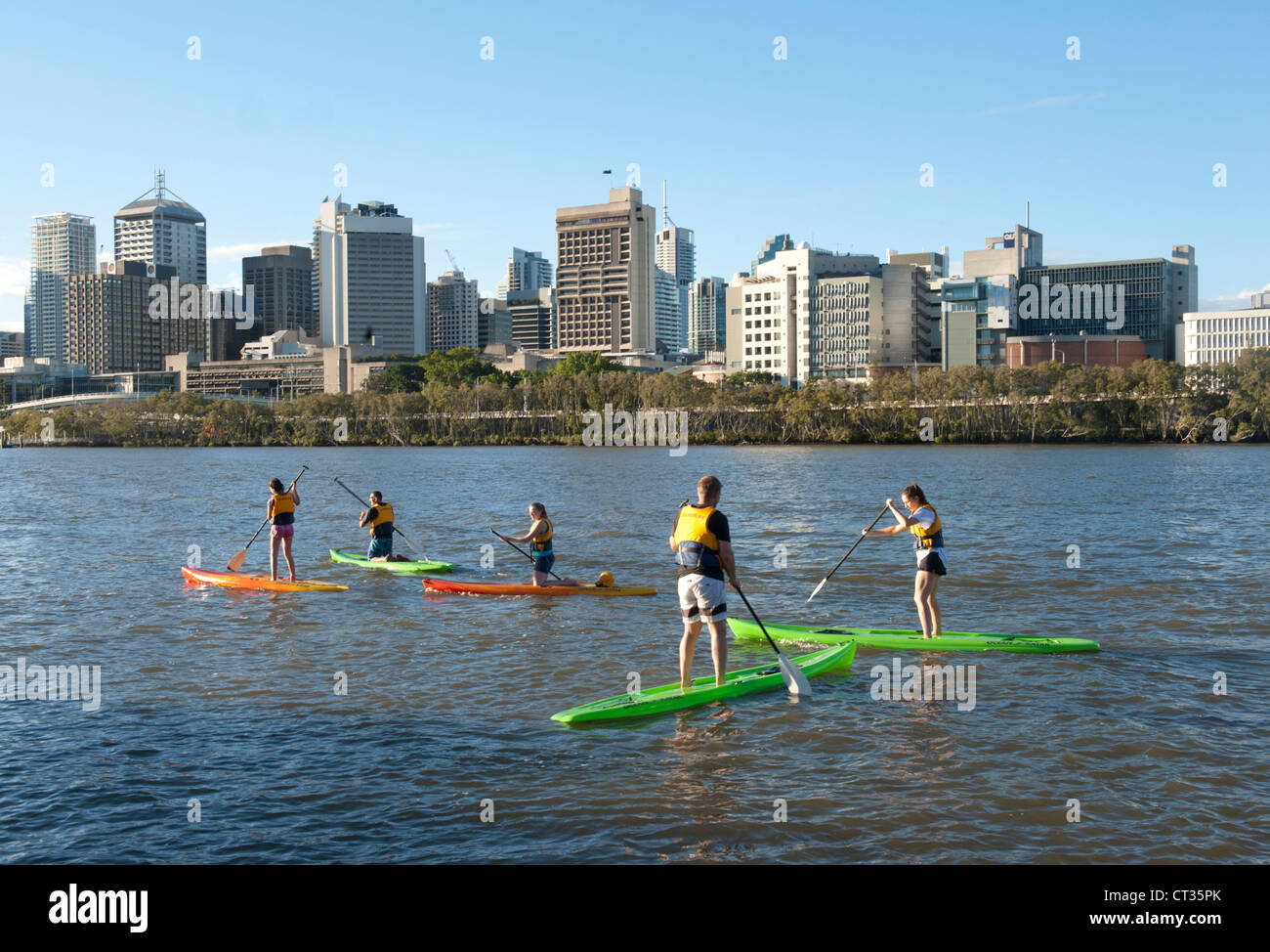 Stand-Up Paddling on Brisbane River with CBD in view, Queensland, Australia - Stock Image