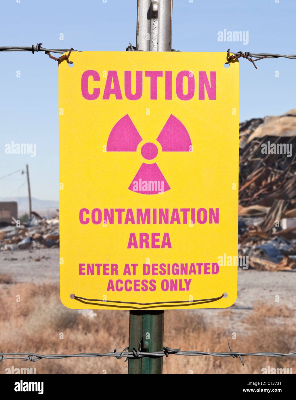 Caution radioactive contamination warning sign with barb wire fence. - Stock Image