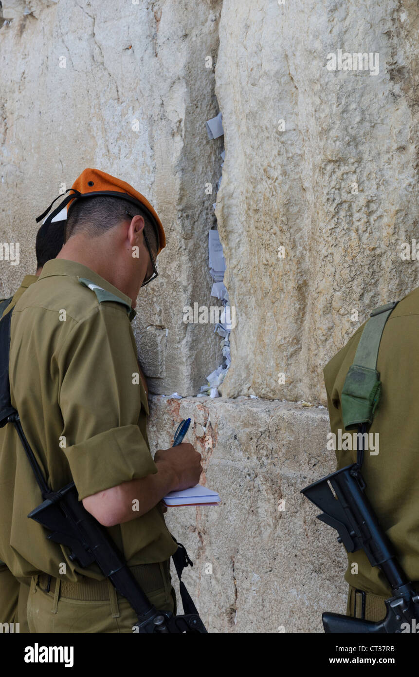 Israeli soldiers writing paper notes to be placed in the wall cracks. Western Wall. Jerusalem Old City. israel. - Stock Image