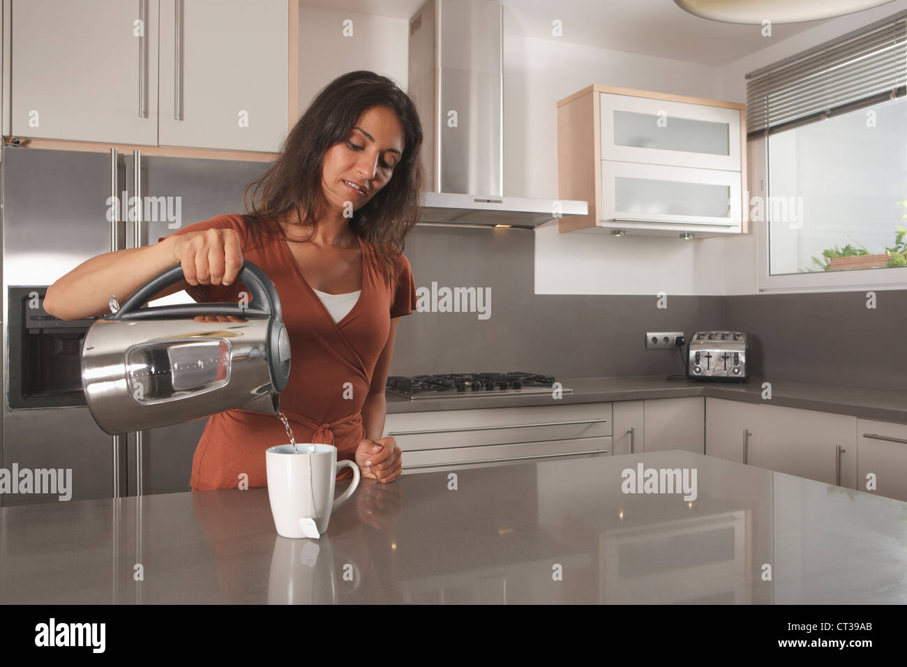 Woman making cup of tea in kitchen - Stock Image
