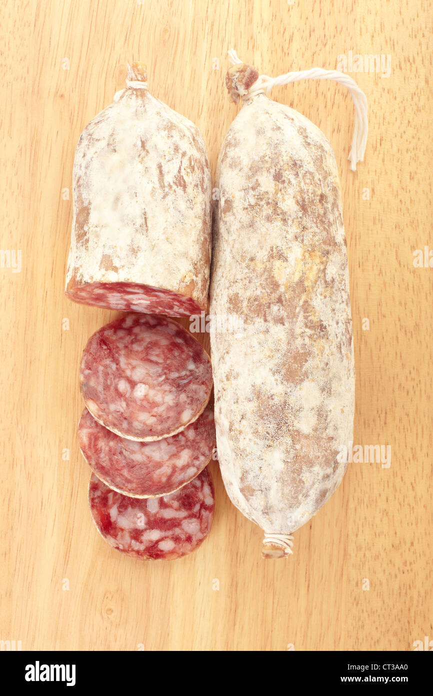 Sliced salami on cutting board - Stock Image
