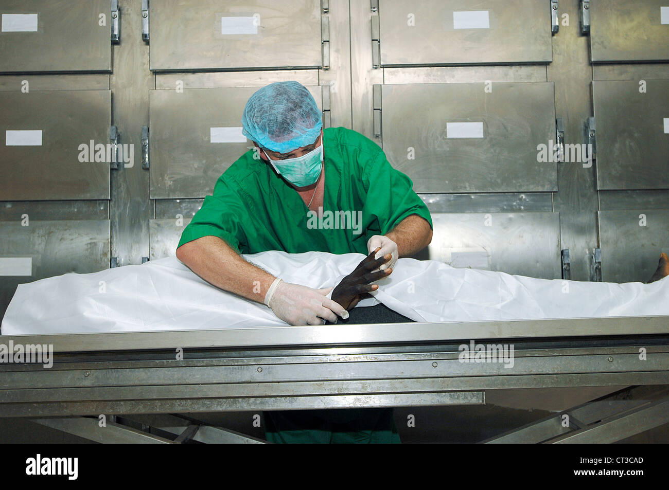 A forensic pathologist inspects the hands and fingers of a corpse. - Stock Image