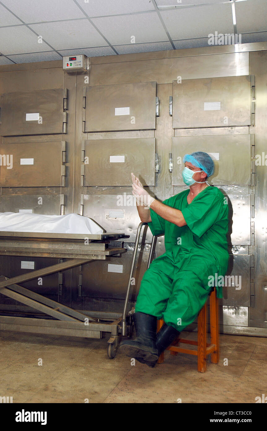A mortuary technician adjusts his gloves, prior to inspecting a corpse. - Stock Image