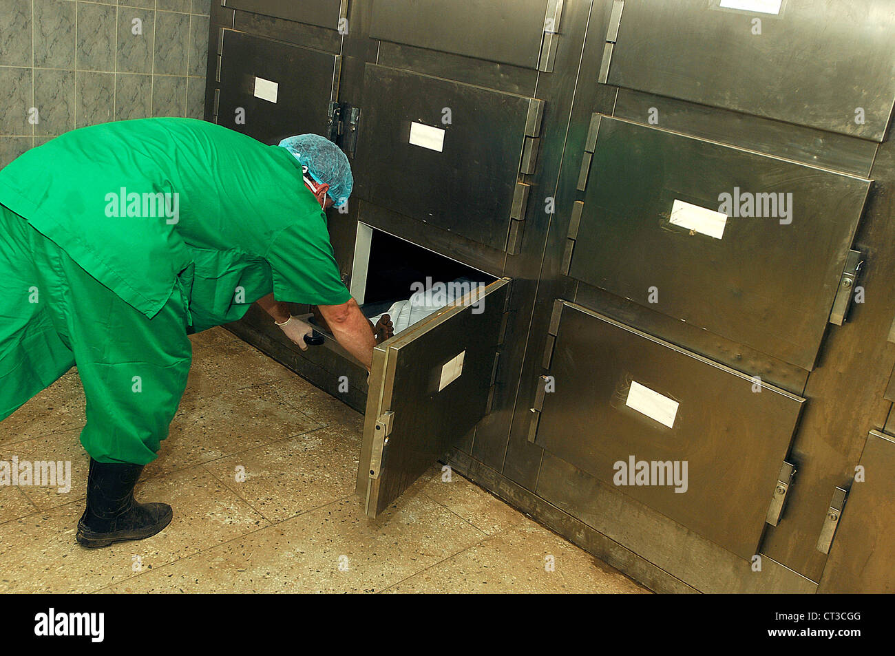 A mortuary technician places a human body in a cold storage facility. - Stock Image