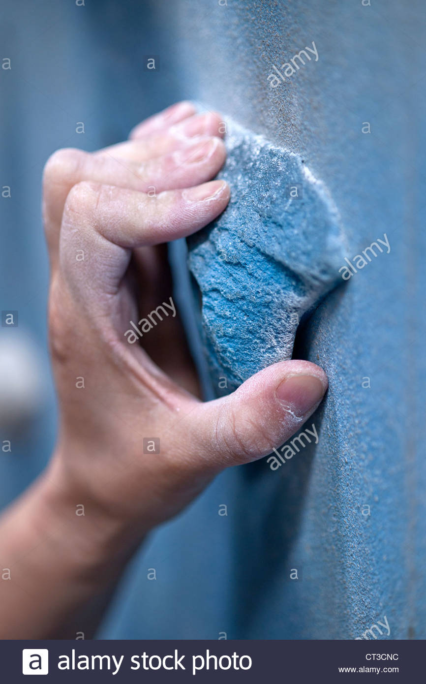Close up of climber gripping rock wall - Stock Image
