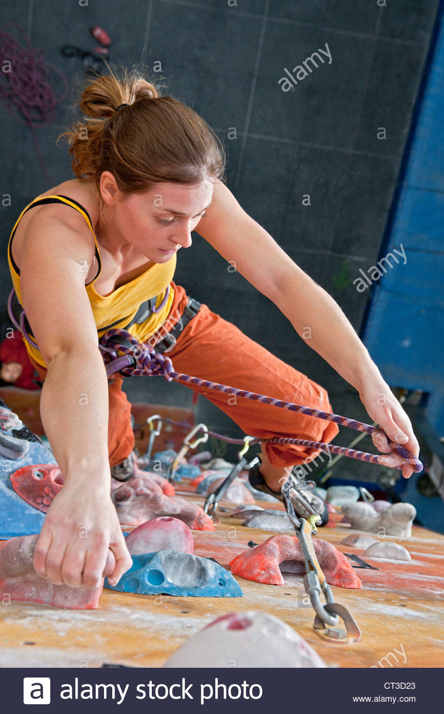 Woman climbing indoor rock wall - Stock Image