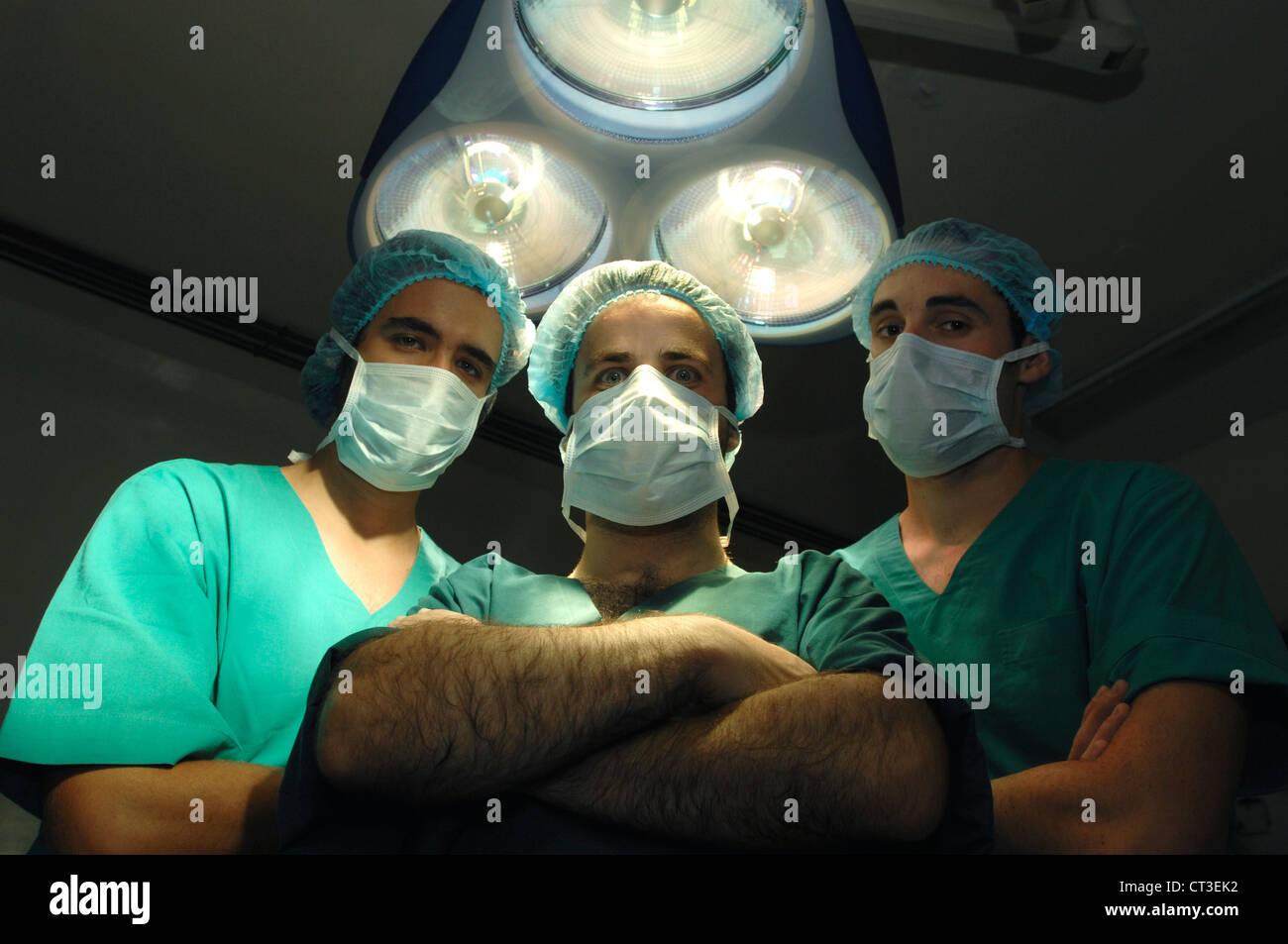 Three surgeons standing underneath a theatre light. - Stock Image