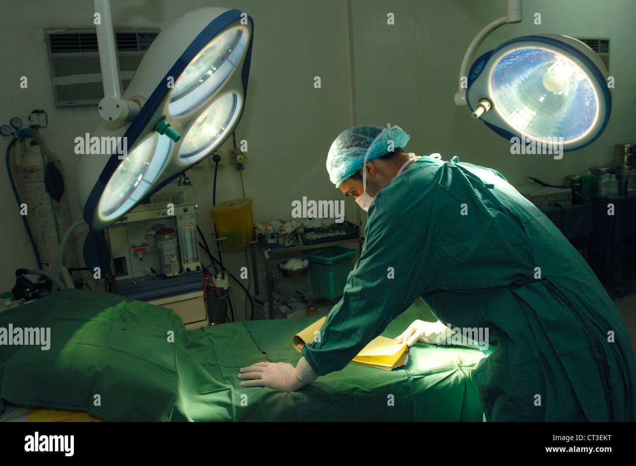 A surgeon looking over patient notes before a procedure. - Stock Image