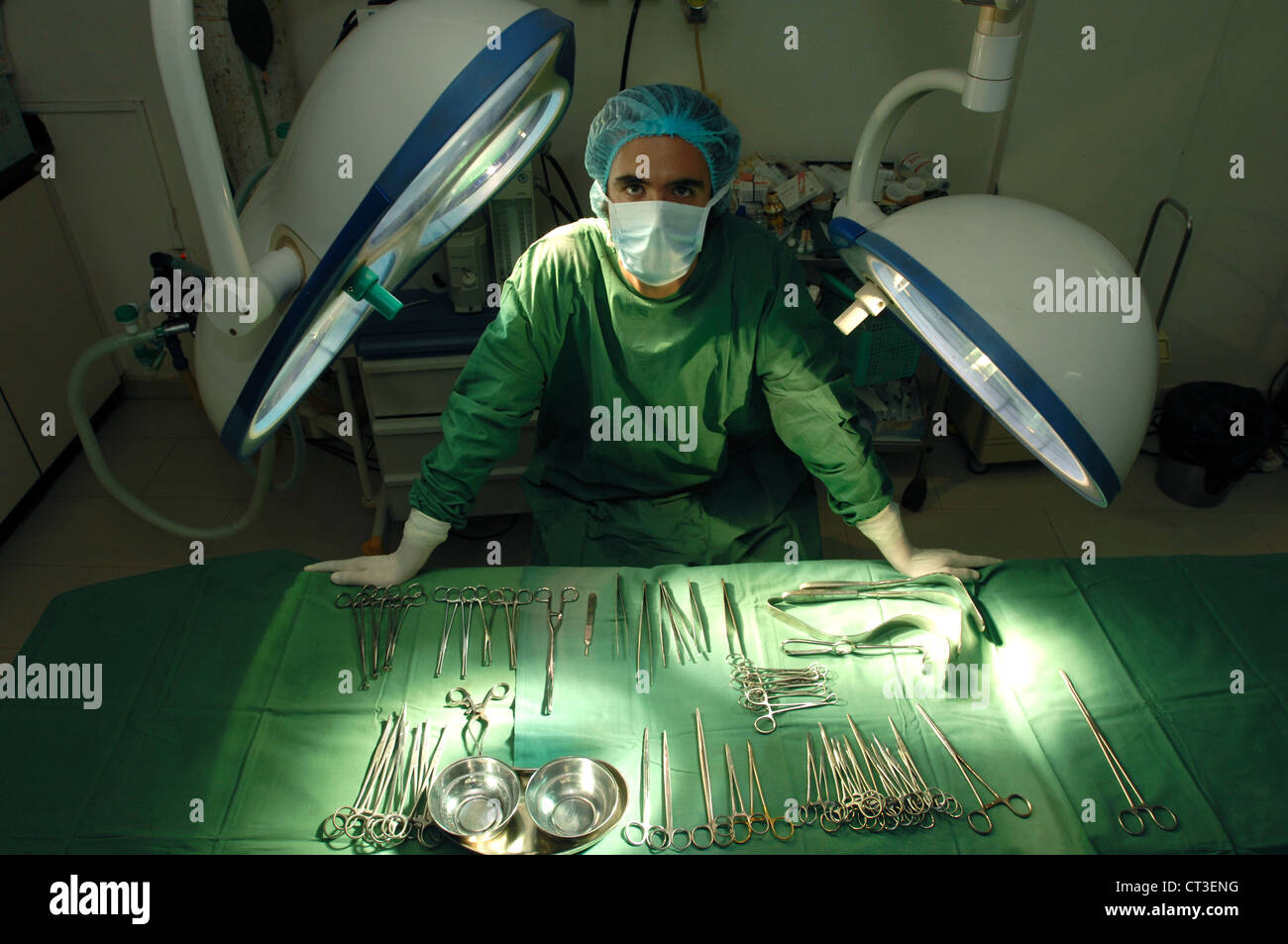 A masked surgeon leaning on a table of sterile surgical tools in a hospital theatre. - Stock Image