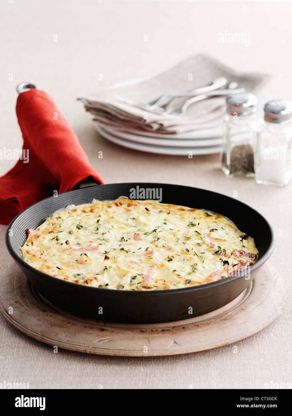 Omelet pan on wooden board - Stock Image