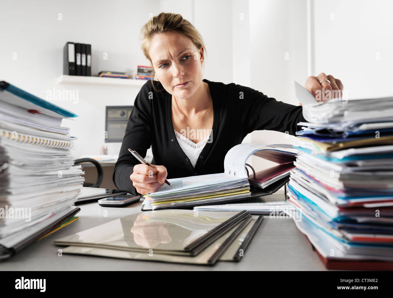 Businesswoman working in office - Stock Image