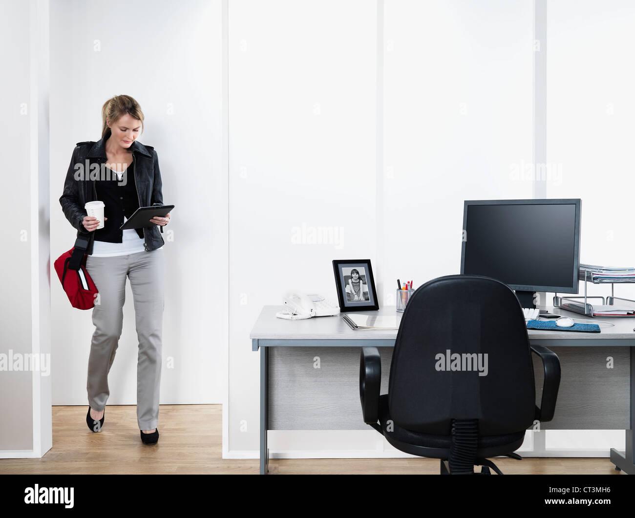 Businesswoman walking into office Stock Photo