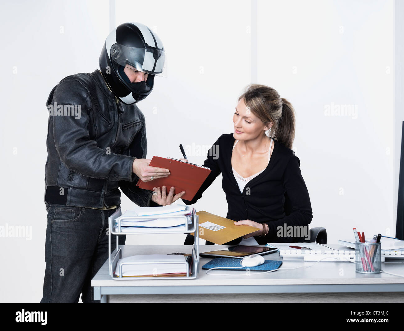 Businesswoman signing for courier Stock Photo