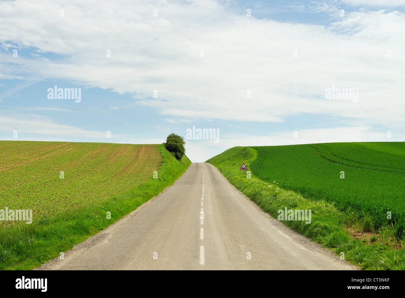 Rural road between crop fields - Stock Image