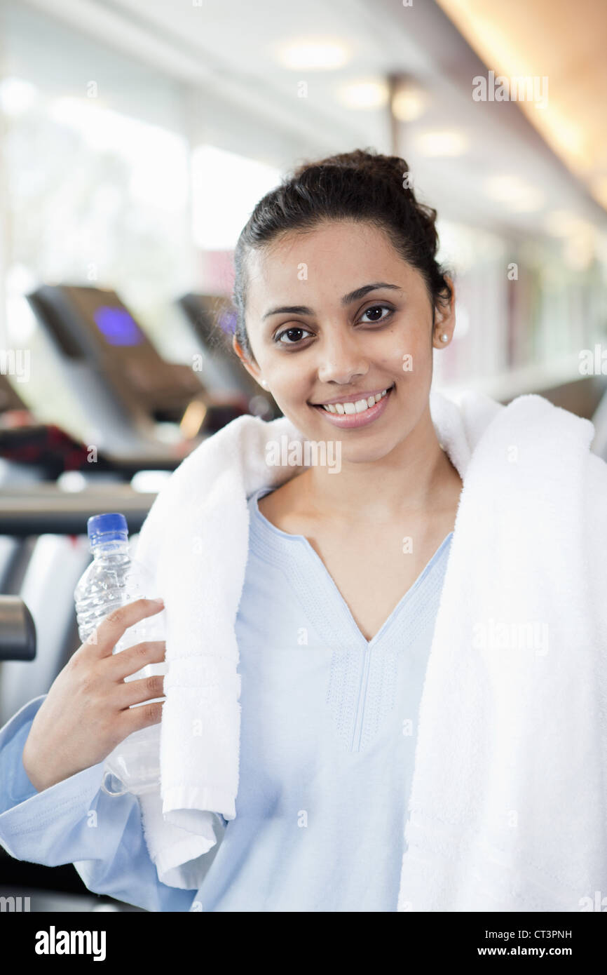 Woman with towel and water bottle in gym Stock Photo