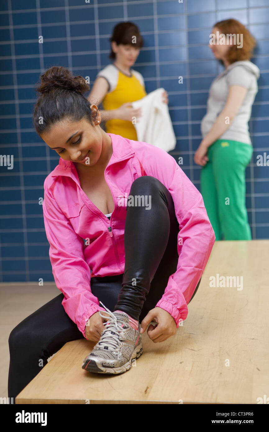 Woman tying her shoes in locker room - Stock Image