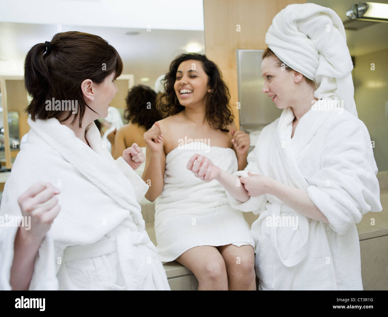 Women wearing towels in locker room - Stock Image