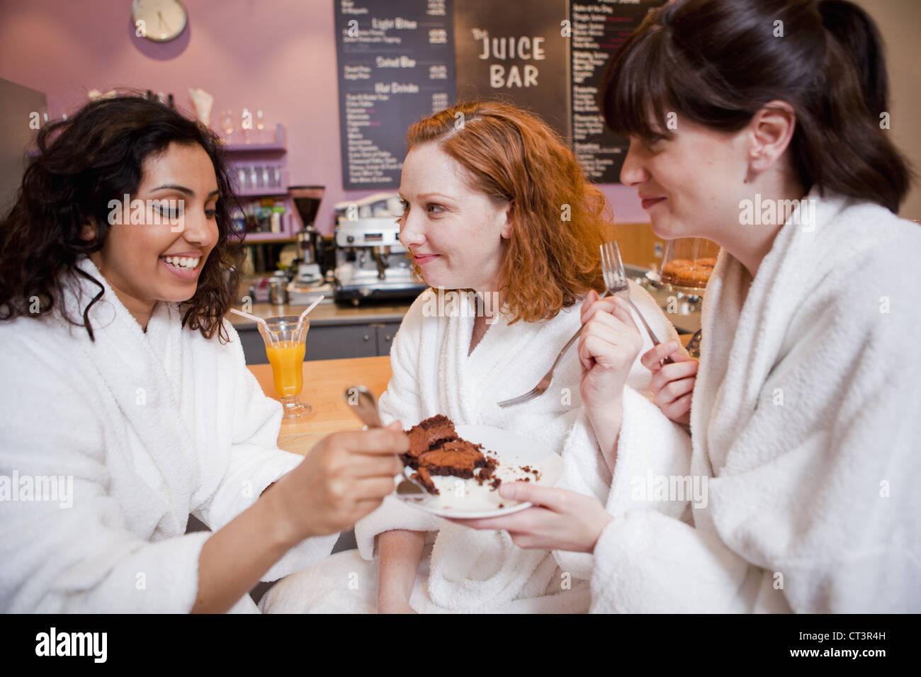 Women having cake in juice bar - Stock Image