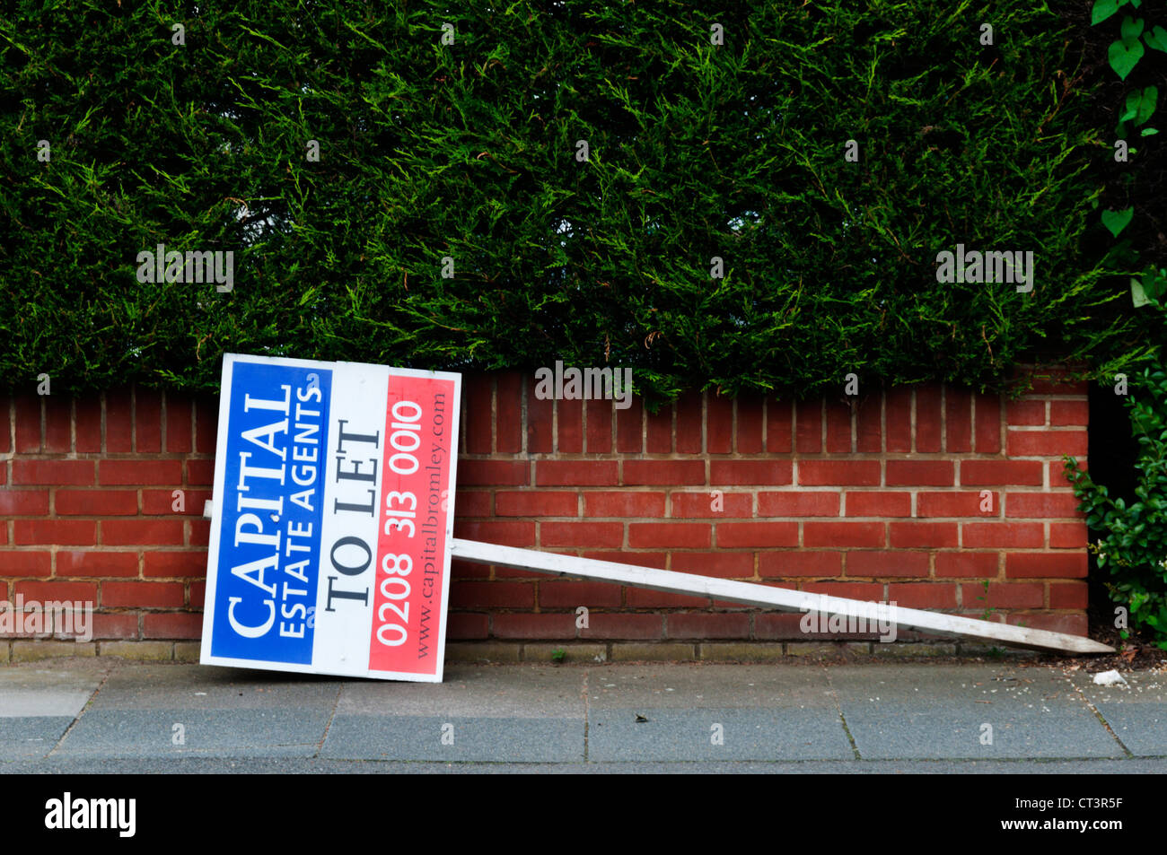 An Estate Agents' board on the pavement leant sideways against a garden wall. - Stock Image