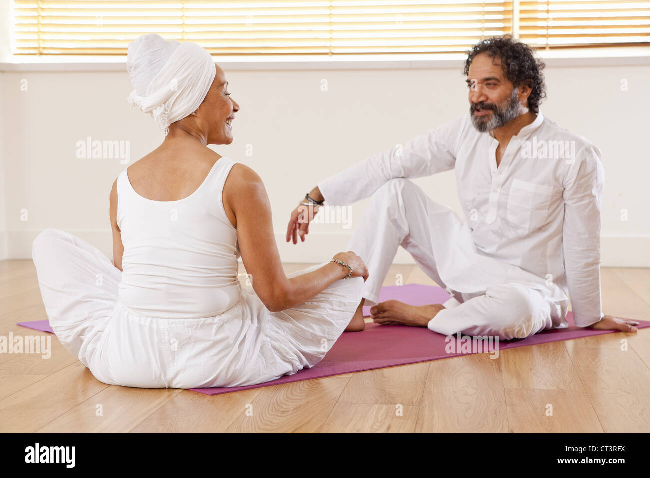 Couple talking on yoga mats - Stock Image
